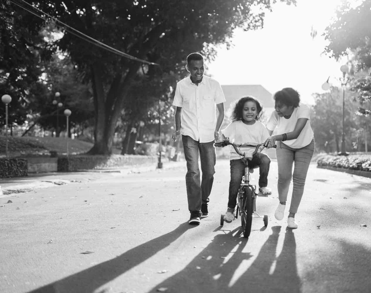 family, with mom and dad teaching child to ride a bike