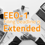 "Image of a desk full of business items and a man in a black suit sitting at desk. Words written across the top of image say ""EEO-1 Filing Deadline is Extended"""