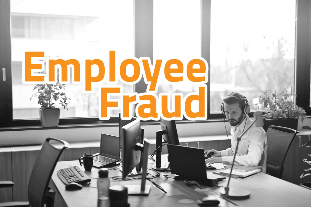 "Image of a young business man sitting at a desk working with the caption, ""employee fraud"" written on top of image."