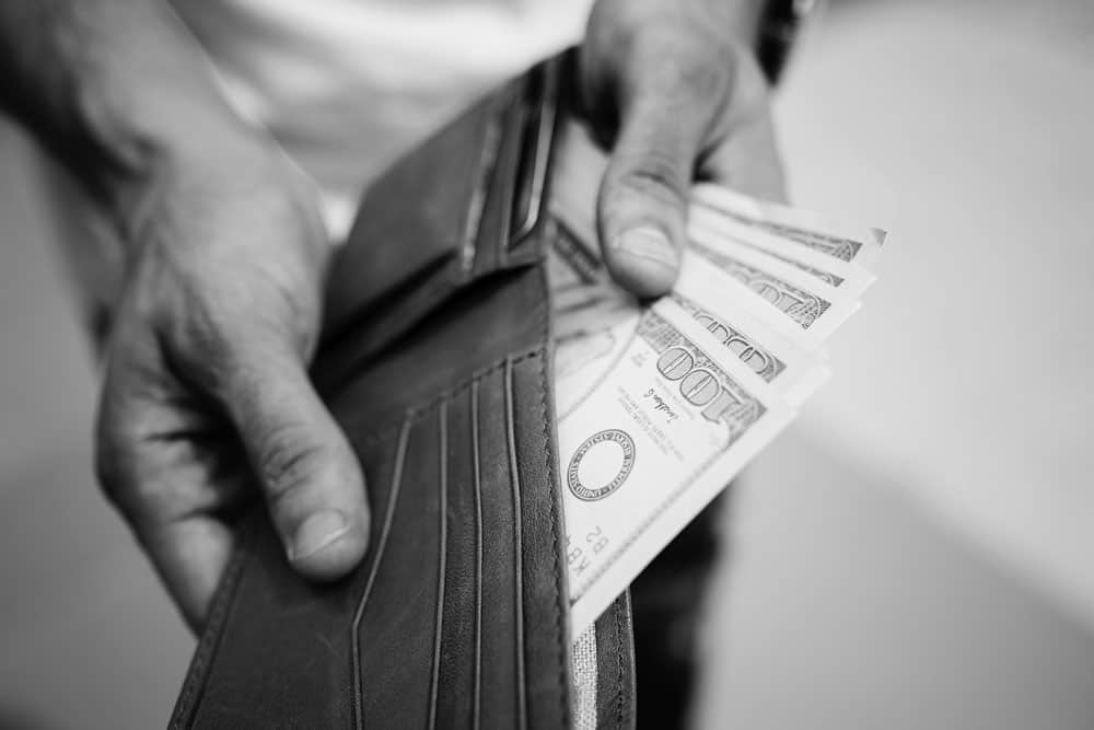 image of a man holding a wallet and pulling out 100 dollar bills