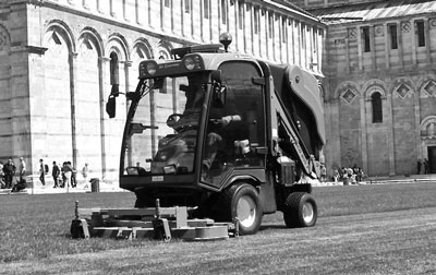 Image of an industrial mower cutting grass in front of a large building