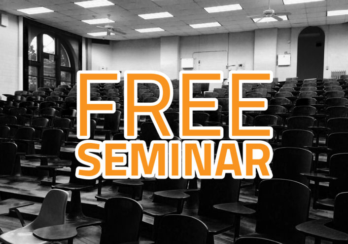 "Picture of a seated auditorium with type written across the front saying, ""free seminar"""