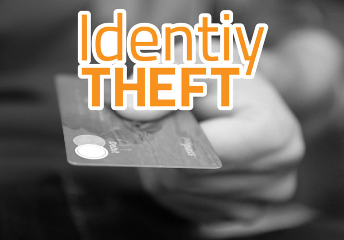 "Image of a hand holding a credit card with the words ""identity theft"" written across the front"