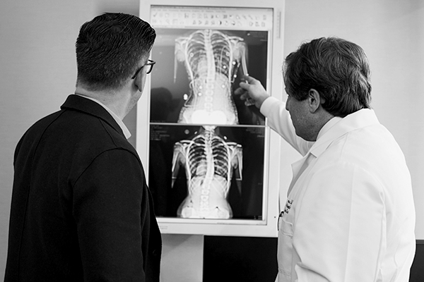 Doctor pointing at a x-ray result next to a man wearing a black suit.